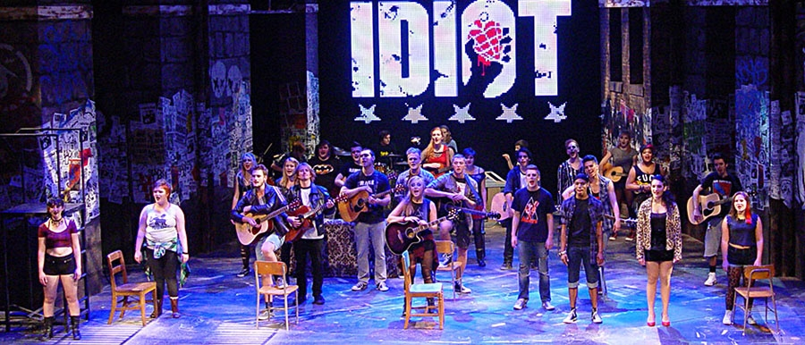 A Scene from AMERICAN IDIOT. Actors on stage playing instruments and singing.