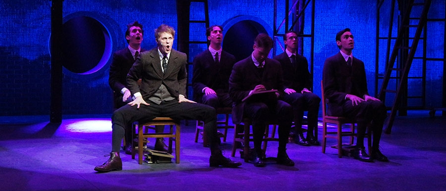A Scene from SPRING AWAKENING. Six people sitting in chairs and singing.